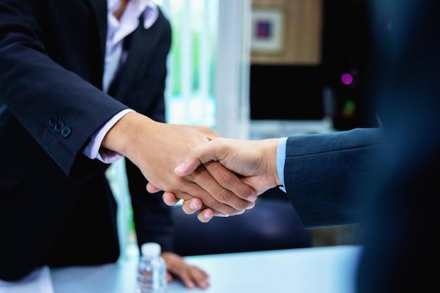 Succesvolle bedrijfsmensen die handen schudden na het sluiten van een overeenkomst