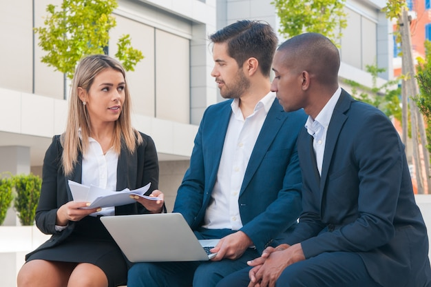 Succesvolle bedrijfsmensen die rapporten in openlucht bespreken