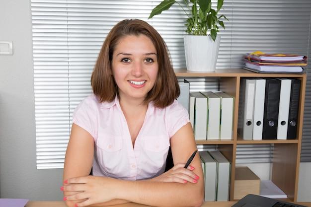 Succesvolle bedrijfsvrouw die en op het kantoor glimlacht werkt