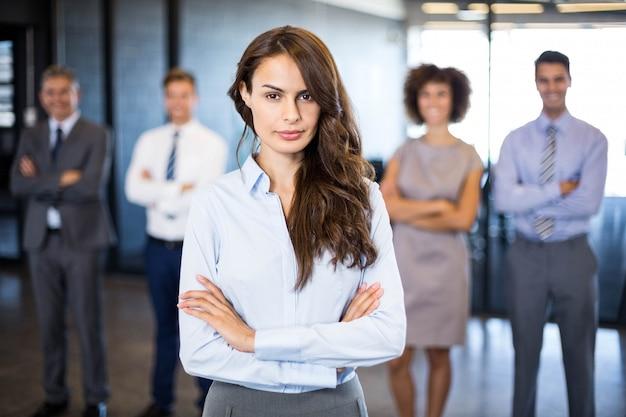Succesvolle bedrijfsvrouw die terwijl haar collega's glimlachen die zich achter hem in bureau bevinden