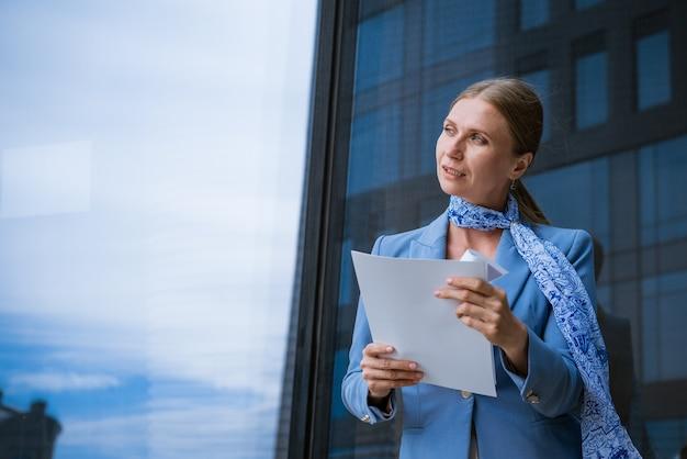 Succesvolle bedrijfsvrouw in blauwe jas houdt documenten in de hand in de buurt van kantoorgebouw