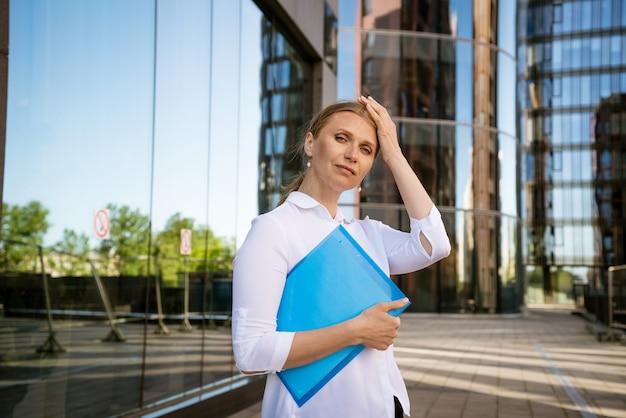 Succesvolle bedrijfsvrouw in wit overhemd met blauwe map voor papieren staat op kantoorgebouw