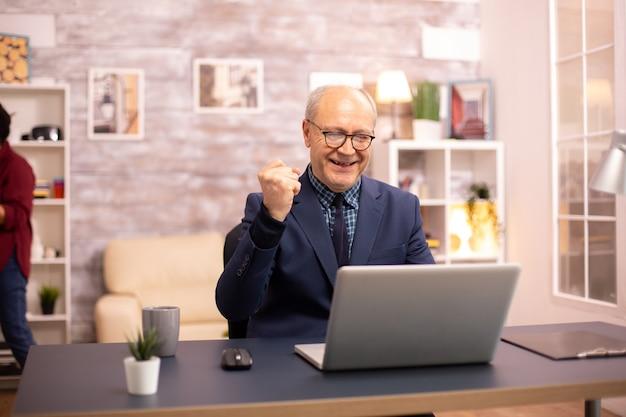 Succesvolle bejaarde in pak die vanuit huis aan een laptop werkt. zijn vrouw is op de achtergrond