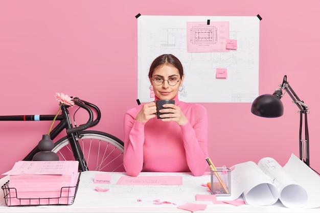 Succesvolle bekwame europese vrouwelijke student van de technische faculteit drinkt warme koffie, werkt aan architecturale projecthoudingen in coworking-ruimte, ziet er direct uit. werkdag op gezellig kantoor