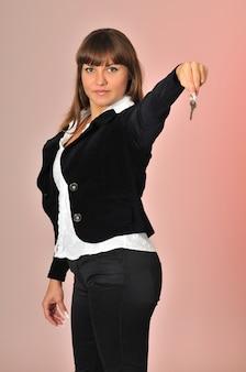 Succesvolle blanke vrouw verkoop agent sleutel in de hand te houden.
