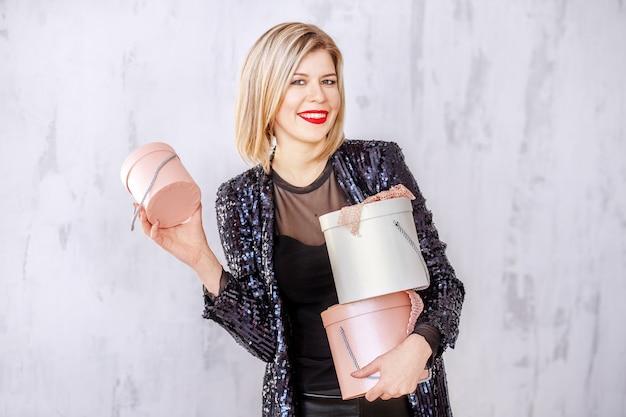 Succesvolle blonde vrouw houdt geschenkdozen