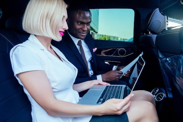 Succesvolle blonde zakenvrouw ondernemer werkgever met make-up in witte zakelijke jurk met een knappe afro-amerikaanse baas man industrieel in zwart stijlvol colbert werken in auto met laptop