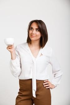 Succesvolle dame baas koffie drinken, glimlachend