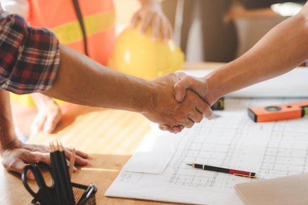 Succesvolle deal, mannelijke architect handen schudden met opdrachtgever in bouwplaats na bevestiging blauwdruk voor renovatie gebouw.