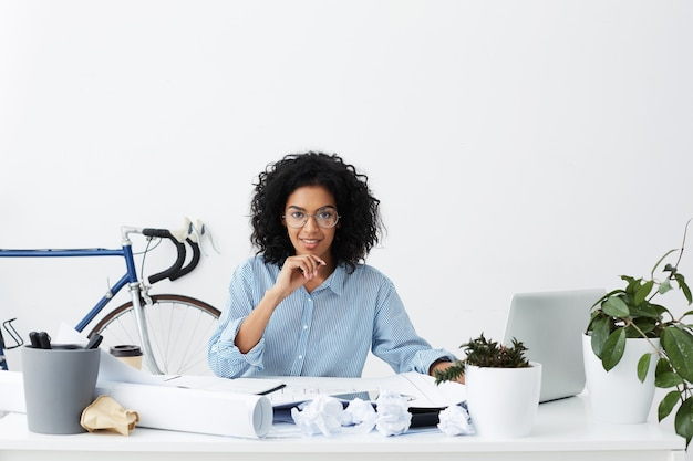 Succesvolle donkere vrouw ingenieur in formele slijtage met pen tijdens het tekenen