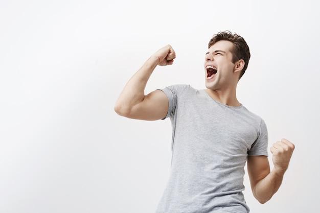 Succesvolle emotionele jonge blanke mannelijke sportman met donker haar ja schreeuwen en gebalde vuisten in de lucht, opgewonden gevoel. mensen, succes, triomf, overwinning, winnen en feest.