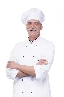 Succesvolle en gelukkige bejaarde chef-kok gekruiste armen, portret op witte muur geïsoleerd