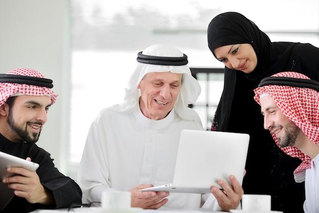 Succesvolle en gelukkige zakelijke arabische mensen zitten voor een vergadering