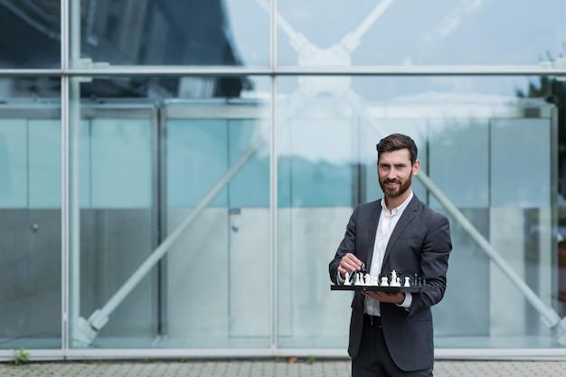 Succesvolle en gelukkige zakenman die naar de camera kijkt en een schaakbord vasthoudt, een winnende bedrijfsstrategie