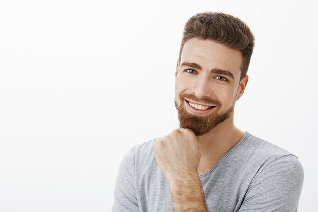 Succesvolle en gelukkige zelfverzekerde mannelijke ondernemer die baard wrijft glimlachend en starend opgetogen met schattige blauwe ogen tevreden zijn met goede resultaten van bedrijf tegen grijze muur