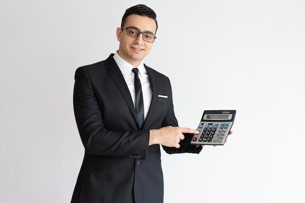 Succesvolle financier die calculator gebruikt en het toont aan camera.