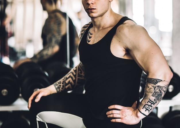 Succesvolle fitnesstrainer die in de sportschool staat.