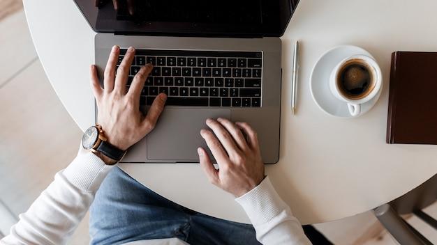 Succesvolle freelancer man in een wit overhemd met chique klok is aan het typen op een metalen moderne laptop zittend in een café