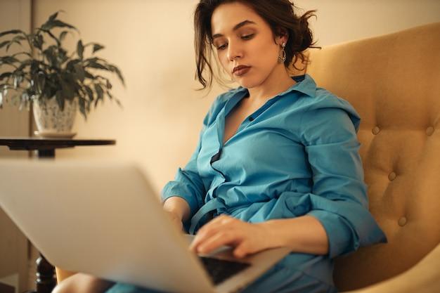 Succesvolle geconcentreerde jonge zakenvrouw in blauwe jurk zittend op de bank met een draagbare computer op haar schoot