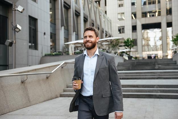 Succesvolle gelukkig man in grijs pak afhaalmaaltijden koffie in de hand te houden, en de trap af te lopen van het moderne zakencentrum in het centrum