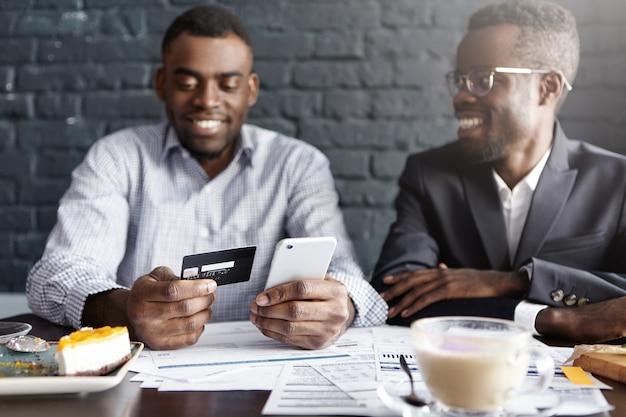Succesvolle gelukkige afrikaans-amerikaanse zakenman die online via internet rekening met creditcard betaalt