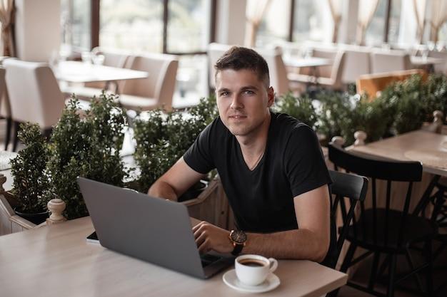 Succesvolle gelukkige jonge zakenman in een zwart t-shirt met een moderne computer zit in een vintage café.