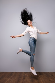 Succesvolle gelukkige mooie vrouw die op grijze ruimte wordt geïsoleerd die omhoog springt