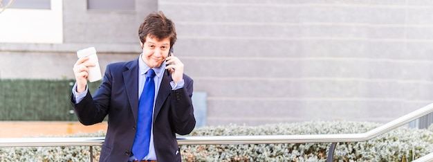 Succesvolle glimlachende aantrekkelijke jonge volwassen zakenman die afhaalmaaltijden koffiekopje toont terwijl hij op smartphone praat. koffie en werkconcept