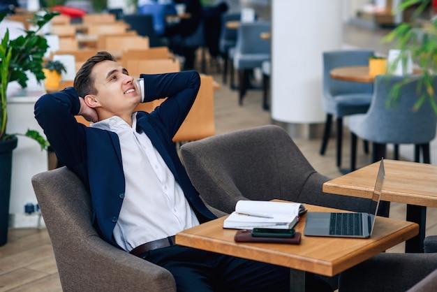 Succesvolle glimlachende zakenman heeft een pauze en voelt geluk