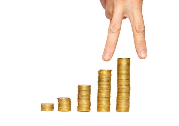 Succesvolle hand bovenop de stapel van gouden munten.