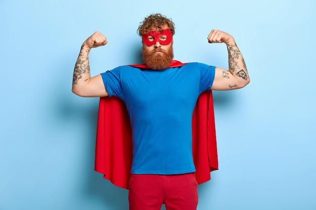 Succesvolle held draagt rood masker en cape, heft armen op