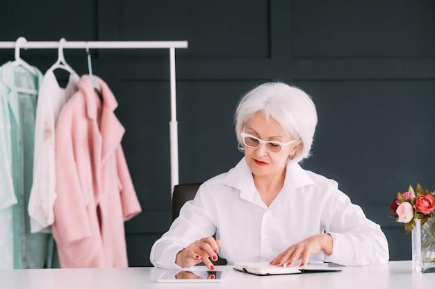 Succesvolle hogere vrouw. modeboetiek bedrijf. doordachte oudere dame bezig met het doorbladeren van tablet op de werkplek.