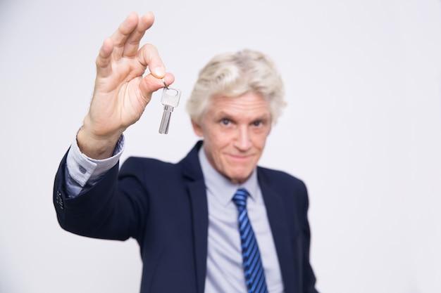 Succesvolle hogere zakenman houden sleutels in de hand
