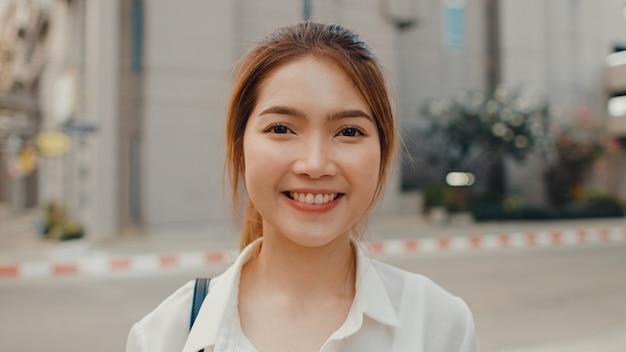 Succesvolle jonge aziatische onderneemster die in de kleren van het manierbureau in de straat glimlachen