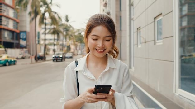 Succesvolle jonge aziatische onderneemster in de kleren van het manierbureau die smartphone gebruiken en sms-bericht typen