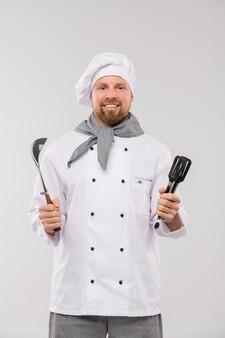 Succesvolle jonge bebaarde chef-kok in uniform keukengerei te houden terwijl u met een glimlach geïsoleerd kijkt