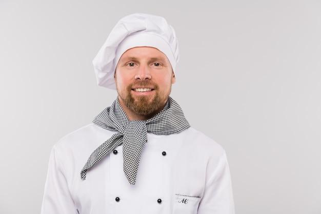 Succesvolle jonge bebaarde chef-kok in uniform op zoek naar jou met brede glimlach geïsoleerd