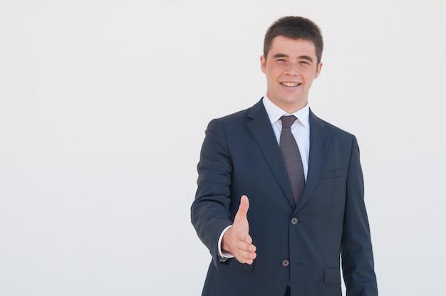 Succesvolle jonge bedrijfsleider die hand aanbiedt voor handdruk