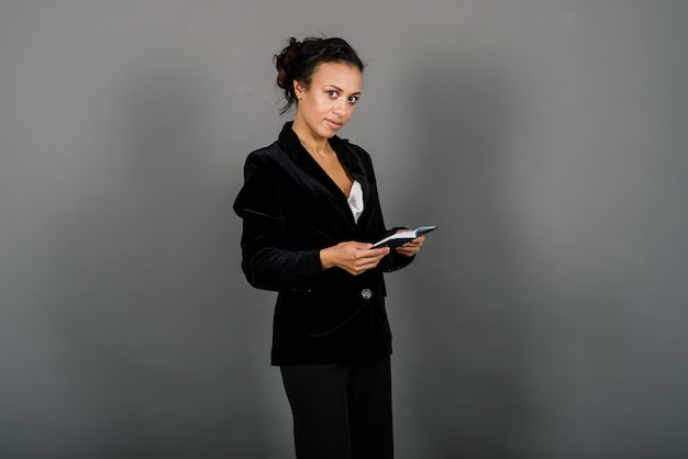 Succesvolle jonge bedrijfsvrouw die met gevouwen handen over grijze achtergrond in studio glimlachen