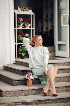 Succesvolle jonge blanke vrouw met lang blond haar die in de buurt van de bloemenwinkel zit en opzij kijkt