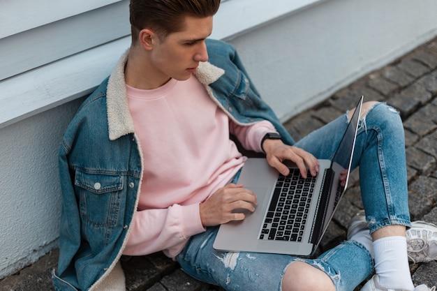Succesvolle jonge freelancer man in stijlvolle denim casual jeans kleding zit met laptop en werkt op afstand aan creatief project. aantrekkelijke modeontwerper typt op het toetsenbord. werk verwijderen.