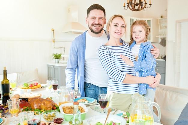 Succesvolle jonge gezin poseren in zonovergoten eetkamer