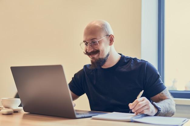Succesvolle jonge man die op laptop kijkt terwijl hij op het kantoor aan huis werkt en aantekeningen maakt freelance concept
