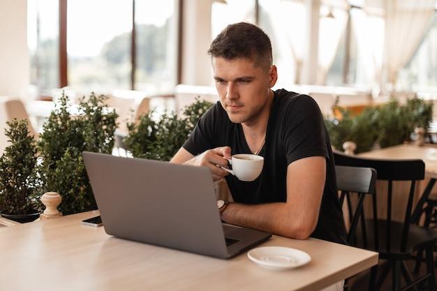 Succesvolle jonge man in een zwart t-shirt zit in een café met een kopje koffie en werkt op een laptop.