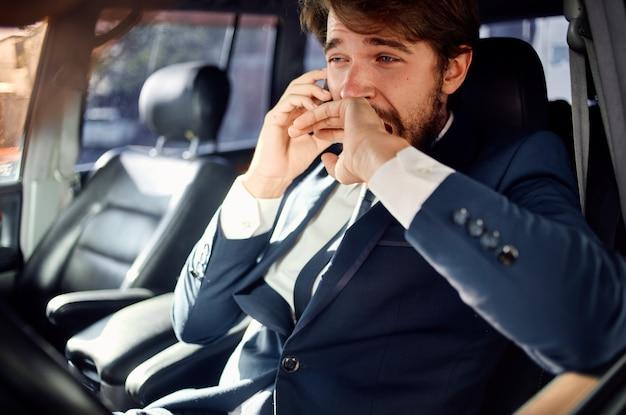 Succesvolle jonge man in pak praten aan de telefoon rijkdom ambtenaar