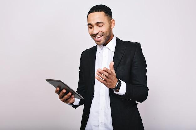 Succesvolle jonge man in wit overhemd, zwarte jas glimlachend naar tablet in handen. leiderschap, geweldige carrière, manager, opgewekte sfeer, kantoorwerk, moderne technologie, glimlachen.