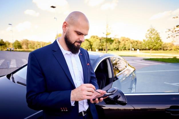 Succesvolle jonge man met een telefoon in de buurt van een auto op een parkeerplaats.