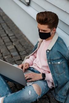 Succesvolle jonge man met kapsel in mode zwart beschermend masker in denim kleding werkt op afstand op moderne laptop buitenshuis. modelman beschermt zichzelf tegen het covid-19-virus en werkt op straat