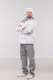 Succesvolle jonge mannelijke chef-kok met zijn armen gekruist door de borst naar jou te kijken terwijl je geïsoleerd staat