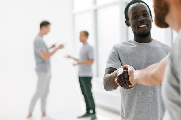 Succesvolle jonge mensen die handen schudden